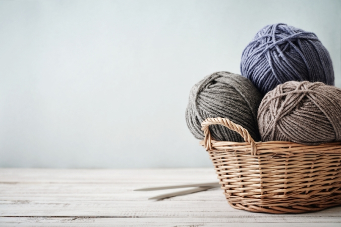 Wool yarn in coils with knitting needles in wicker basket on light blue background