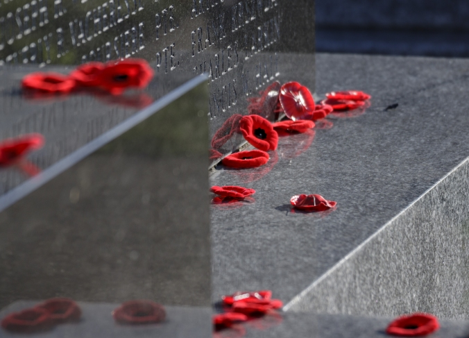 SYDNEY, NOVA SCOTIA, CANADA - NOVEMBER 11, 2014: Poppies placed at the base of a war memorial in Sydney Nova Scotia Canada, November 11th, Remembrance Day, 2014.