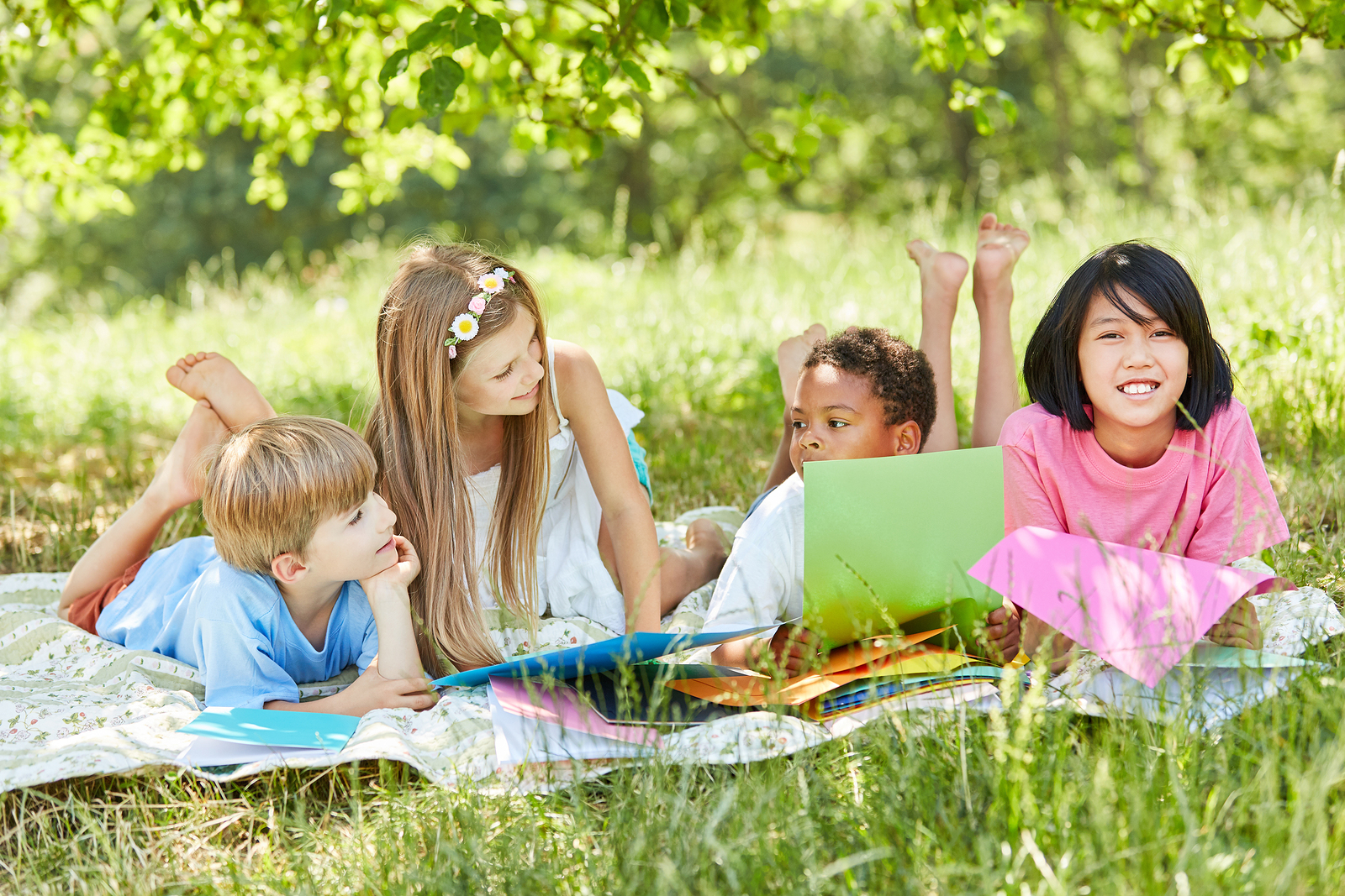 Multicultural group of children on a meadow in summer on vacatio