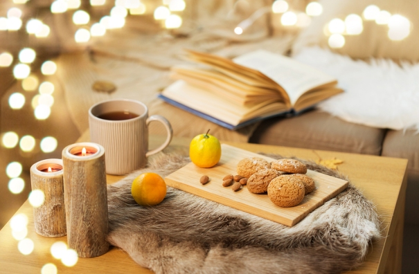 hygge and cozy home concept - oatmeal cookies, lemon tea and can