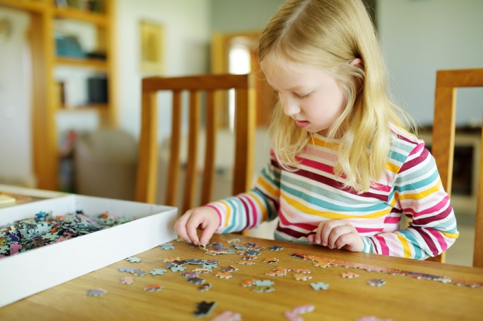 Cute Young Girl Playing Puzzles At Home. Child Connecting Jigsaw