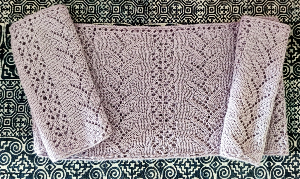 A lavender lace cowl lies flat on a table covered with a mosaic tablecloth.