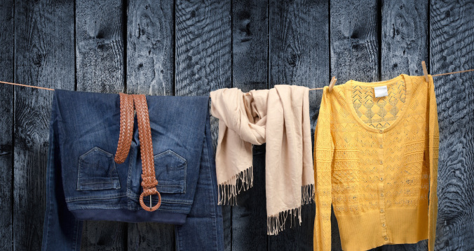 Women's fall clothing on a clothesline; a pair of jeans, a taupe scarf, a yellow sweater.