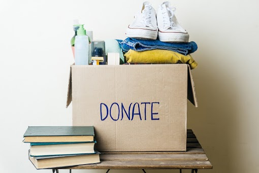 """A box of clothing, books, shoes and other items marked """"Donate"""""""