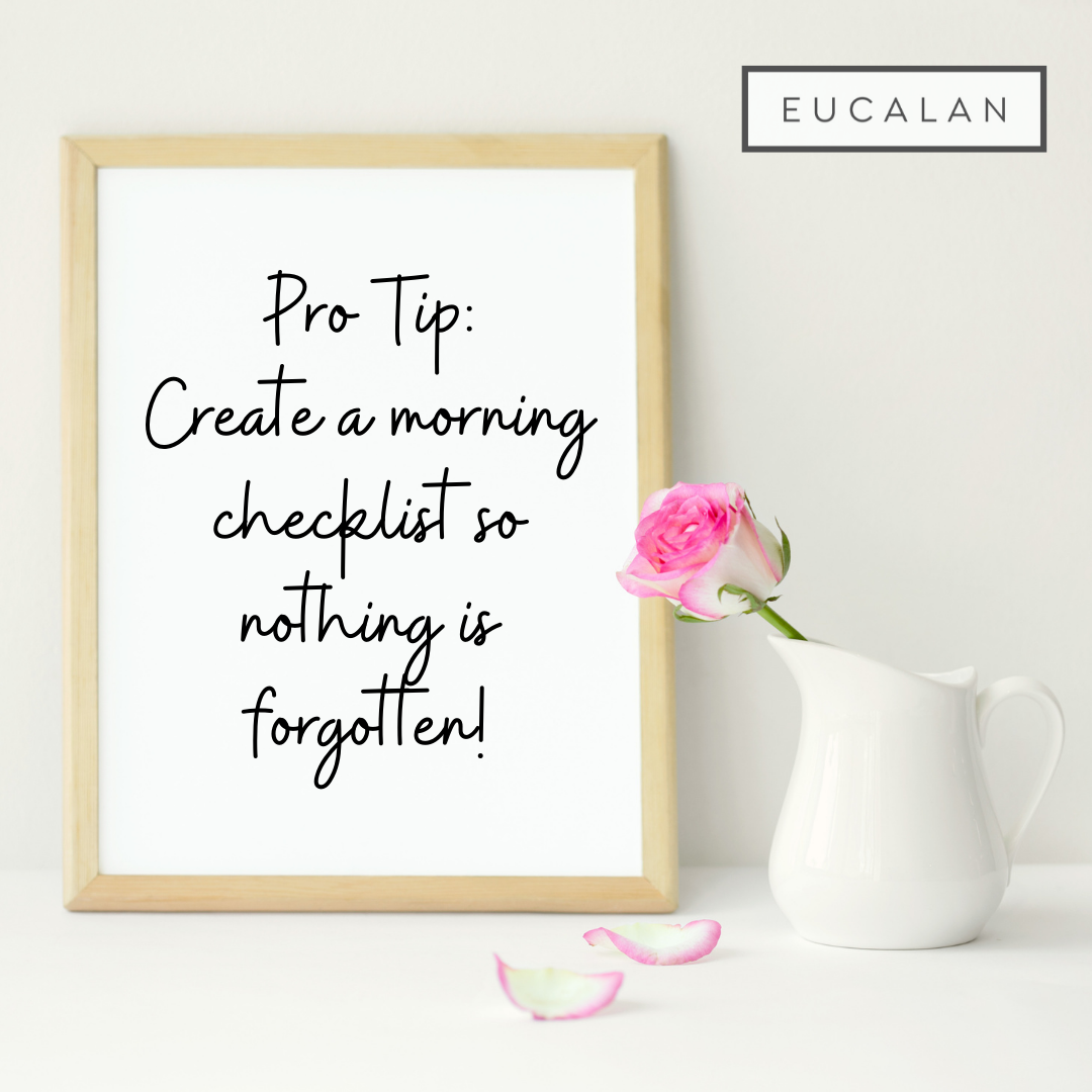"""A small whiteboard sits next to a white pitcher with a pink-tipped rose in it. Text reads """"Pro tip: Create a morning checklist so nothing is forgotten."""""""